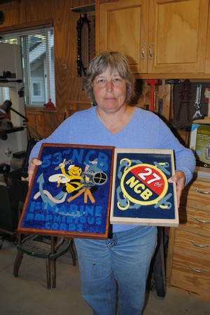 Patty Kreider of Ventura, a member of the Channel Islands Carvers, shows the two plaques she carved for the Seabee Museum.